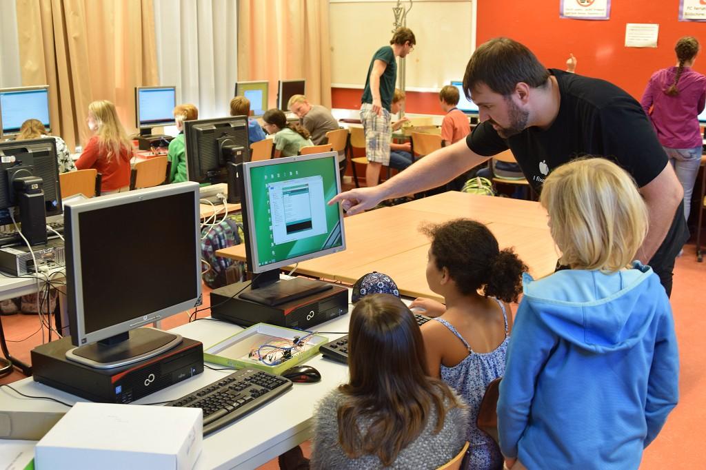 Sebastian Huhn erklärt ein paar Kindern wie man programmiert