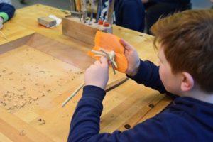 Paul bearbeitet das Holz mit Sandpapier