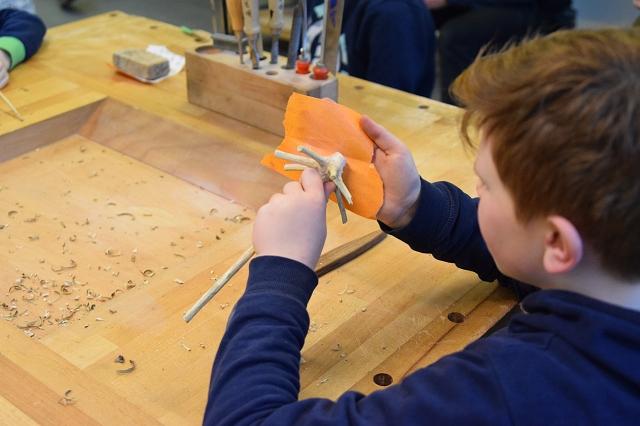 Paul bearbeitet das Holz mit Sandpapier.
