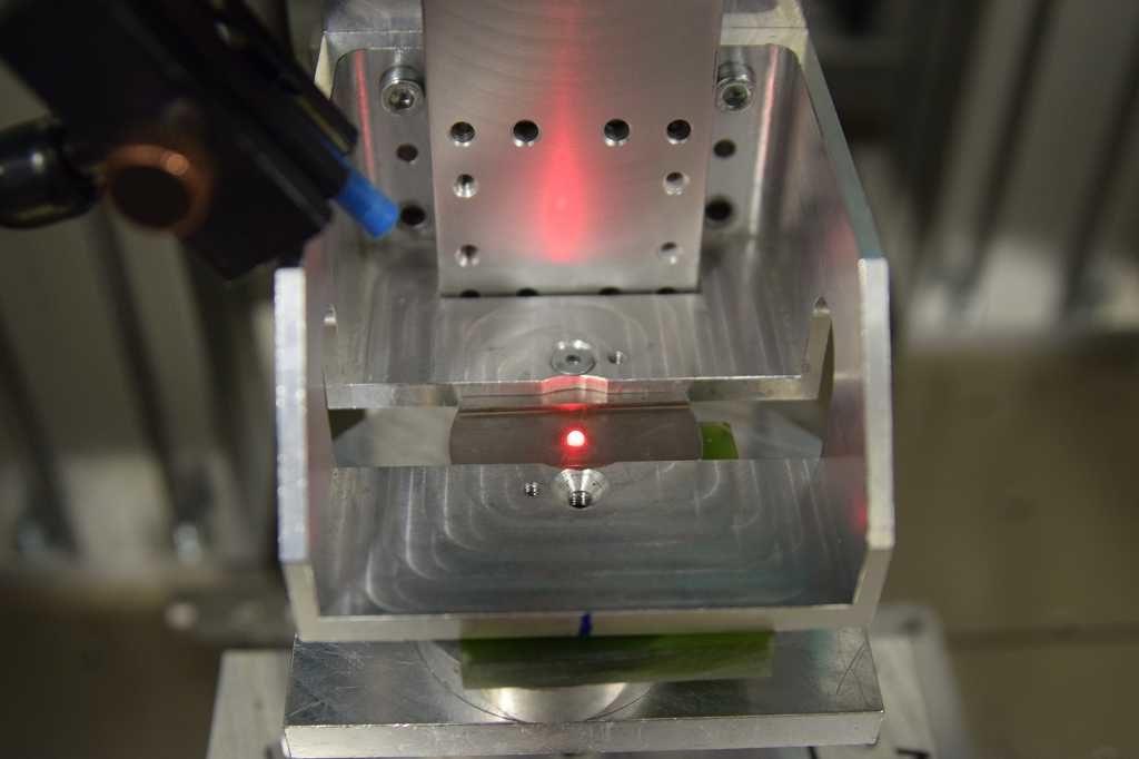 Der Laser bestrahlt die Keramikkugel, darunter die grüne Probeneinheit.