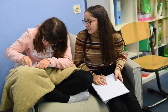 Zwei Schülerinnen malen Computer auf ein Blatt Papier.